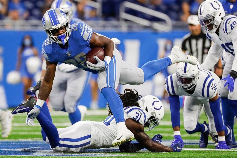 Detroit Lions running back Jermar Jefferson (28) runs against Indianapolis Colts safety Shawn Davis (31) during the first half of a preseason game at Ford Field in Detroit, Friday, August 27, 2021.