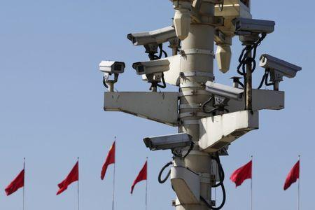 Security cameras in Tiananmen square are seen in front of flags on the Great Hall of the People where the National People's Congress (NPC) is being held, in Beijing