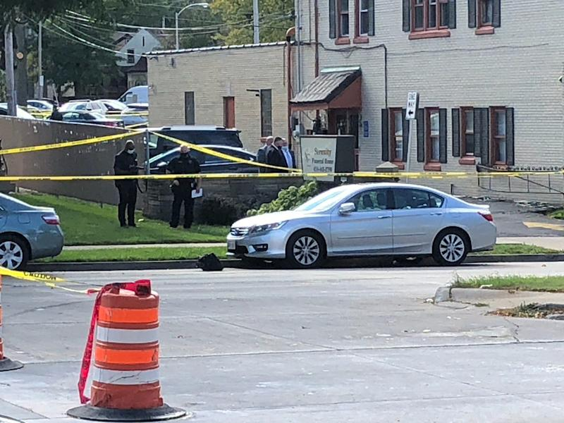 Investigators gather outside Serenity Funeral Home on West Fond du Lac Avenue in Milwaukee after seven people were injured in a shooting there Wednesday.