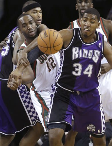 Milwaukee Bucks forward Luc Mbah a Moute, of Cameroon, left, and Sacramento Kings forward Jason Thompson, right, battle for the ball during the first quarter of an NBA basketball game in Sacramento, Calif., Sunday, March 10, 2013.(AP Photo/Rich Pedroncelli)