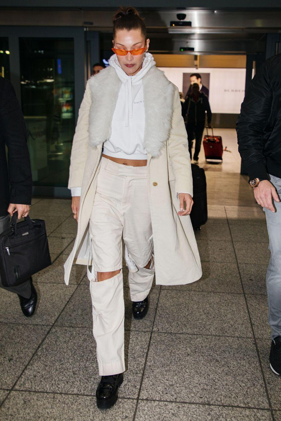 <p>In a cream corduroy coat with a fur collar, cropped hoodie, white ripped jeans by Private Policy, black creepers, and orange sunglasses at the airport in Dubai.</p>