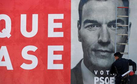 A worker places an electoral poster of Spain's Socialist leader and current Prime Minister Pedro Sanchez in La Fresneda
