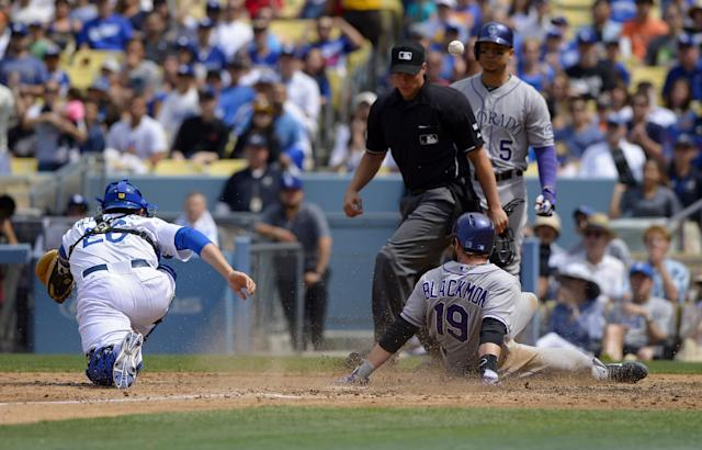 Colorado Rockies' Charlie Blackmon, lower right, scores after Brandon Barnes was caught stealing second as the ball goes past Los Angeles Dodgers catcher Tim Federowicz, left, while home plate umpire Stu Scheurwater and Rockies' Carlos Gonzalez look on during the fifth inning of a baseball game, Sunday, April 27, 2014, in Los Angeles. (AP Photo/Mark J. Terrill)