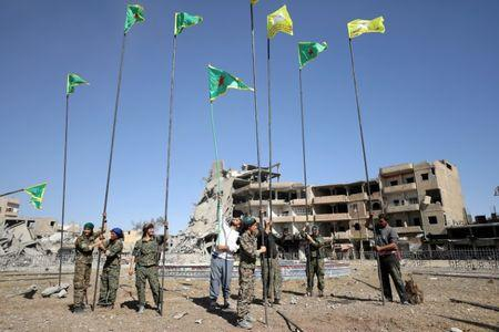 FILE PHOTO: Fighters of Syrian Democratic Forces place flags at Naim Square after liberating Raqqa, Syria October 18, 2017.