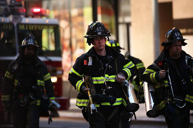 NEW YORK, NY - JUNE 12: Firefighters return to their trucks after rescuing two window washers left dangling from broken scaffolding on the top of the 46-story Hearst Tower on June 12, 2013 in New York City. The workers, who were servicing the window-washing equipment when the scaffolding broke, were left dangling 500 feet above Eighth Avenue. Firefighters and NYPD emergency service unit officers were were able to rescue the men as hundreds of onlookers gazed up from the street. (Photo by Spencer Platt/Getty Images)