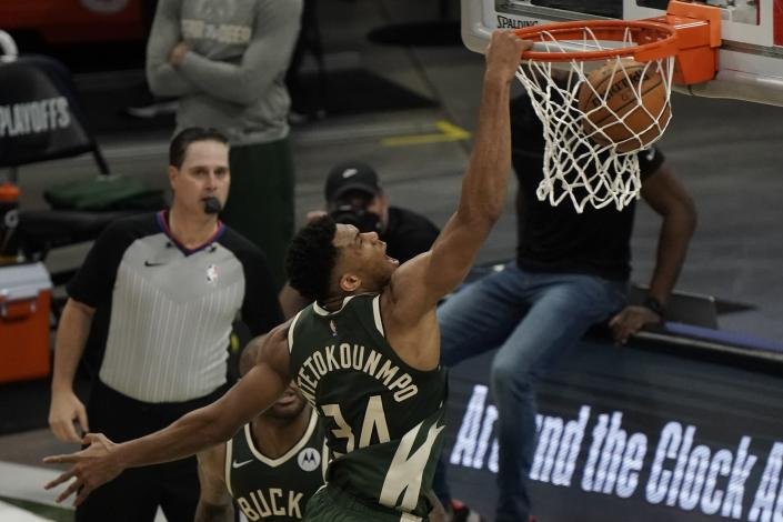 Milwaukee Bucks' Giannis Antetokounmpo dunks during the first half of Game 1 of their NBA basketball first-round playoff series against the Miami Heat Saturday, May 22, 2021, in Milwaukee. (AP Photo/Morry Gash)