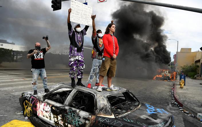Protesters stand atop a burned, graffiti-covered LAPD cruiser. Flames rise from another cruiser nearby.