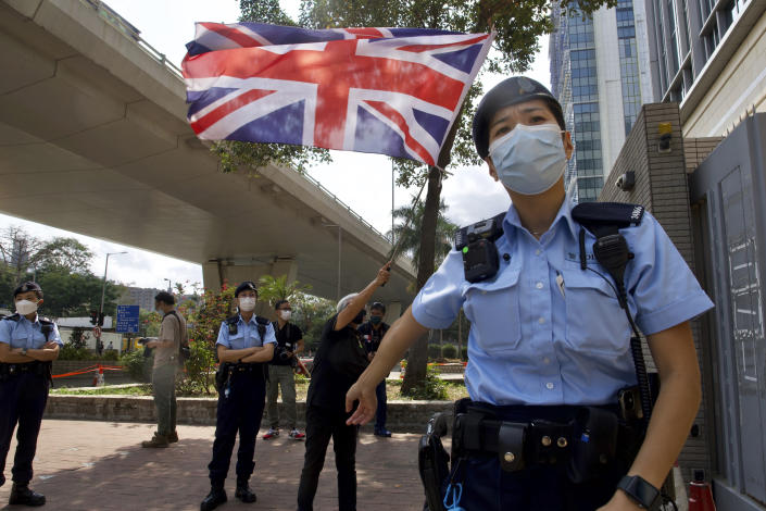 A pro-democracy supporter waves a British flag as police officers stand guard outside a court in Hong Kong Thursday, April 1, 2021. Seven pro-democracy advocates, including media tycoon Jimmy Lai and veteran of the city's democracy movement Martin Lee, are expected to be handed a verdict for organizing and participating in an illegal assembly during massive anti-government protests in 2019 as Hong Kong continues its crackdown on dissent. (AP Photo/Vincent Yu)