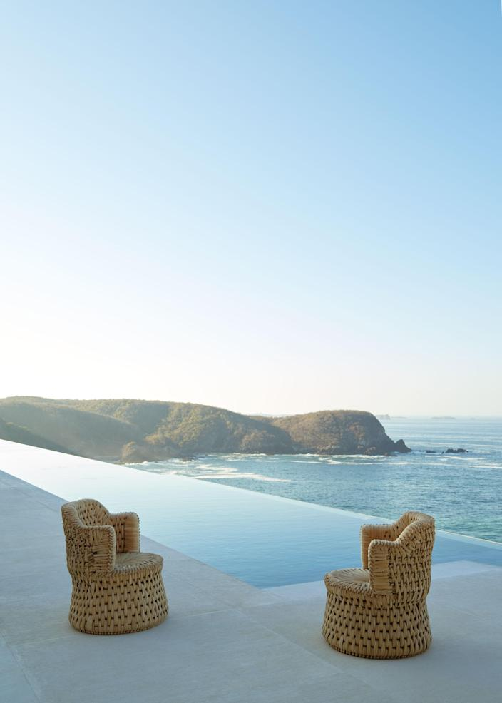 Two woven tule chairs by Txt.ure sit next to the pool.