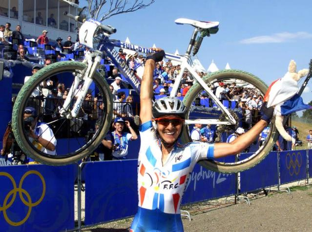 FILE PHOTO: Miguel Martinez of France holds his bike over his head as he celebrates his gold medal win in the m..