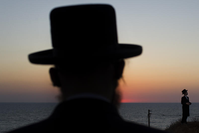 Ultra-Orthodox Jews of the Hassidic sect Vizhnitz gather on a hill overlooking the Mediterranean sea as they participate in a Tashlich ceremony in Herzeliya, Israel, Thursday, Sept. 12, 2013. Tashlich, which means 'to cast away' in Hebrew, is the practice by which Jews go to a large flowing body of water and symbolically 'throw away' their sins by throwing a piece of bread, or similar food, into the water before the Jewish holiday of Yom Kippur, which starts on Friday. (AP Photo/Bernat Armangue)