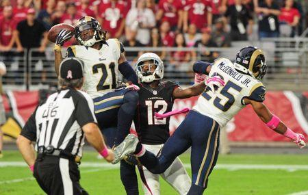 Oct 4, 2015; Glendale, AZ, USA; St. Louis Rams cornerback Janoris Jenkins (21) intercepts a pass intended for Arizona Cardinals wide receiver John Brown (12) as strong safety T.J. McDonald (25) defends and back judge Perry Paganelli (46) watches during the first half at University of Phoenix Stadium. Mandatory Credit: Matt Kartozian-USA TODAY Sports / Reuters Picture Supplied by Action Images