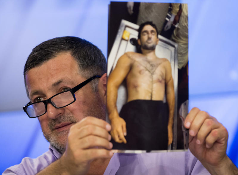 "Abdul-Baki Todashev holds a photo he claims is of his dead son Ibragim Todashev, during a news conference in Moscow, Russia, Thursday, May 30, 2013. The father of a Chechen immigrant killed in Florida while being interrogated by the FBI about his ties to a Boston Marathon bombings suspect says agents killed his son ""execution style."" Abdul-Baki Todashev showed journalists 16 photographs on Thursday of his son, Ibragim, in the morgue with what he said were six gunshot wounds to his torso and one to the back of the head. He said the pictures were taken by his son's friend Khusen Taramov. (AP Photo/Alexander Zemlianichenko)"