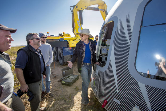 In this undated photo made available by Blue Origin, Jeff Bezos, center, and others inspect Crew Capsule 2.0 after touchdown in West Texas. When Blue Origin launches people into space for the first time, Bezos will be on board. No test pilots or flight engineers for the Tuesday, July 20, 2021 debut flight from West Texas - just Bezos, his brother, an 82-year-old aviation pioneer and a teenager. (Blue Origin via AP)