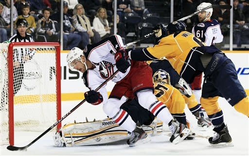 Columbus Blue Jackets center Jeff Carter, left, scores against Nashville Predators goalie Pekka Rinne (35), of Finland, for his third goal of the game to earn a hat trick in the first period of an NHL hockey game on Thursday, Dec. 22, 2011, in Nashville, Tenn. Defending for the Predators at right is Shea Weber (6). (AP Photo/Mark Humphrey)