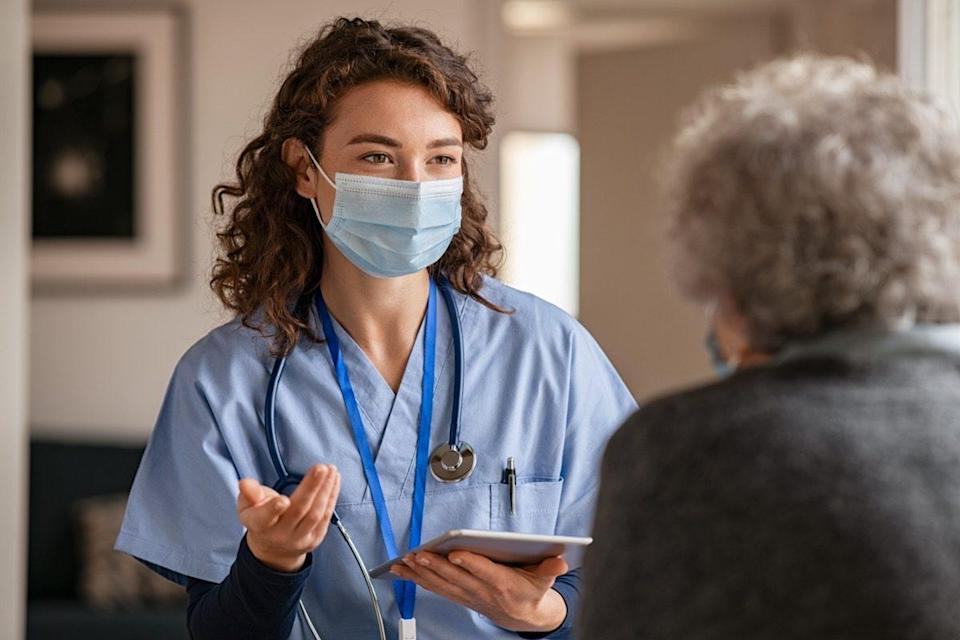 Doctor wearing safety protective mask supporting and cheering up senior patient