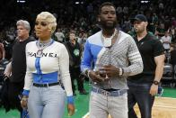 Rapper Gucci Mane and his wife, Keyshia Ka'Oir, walk off the court at halftime while attending Game 3 of a second-round NBA basketball playoff series between the Boston Celtics and the Milwaukee Bucks in Boston, Friday, May 3, 2019. (AP Photo/Michael Dwyer)