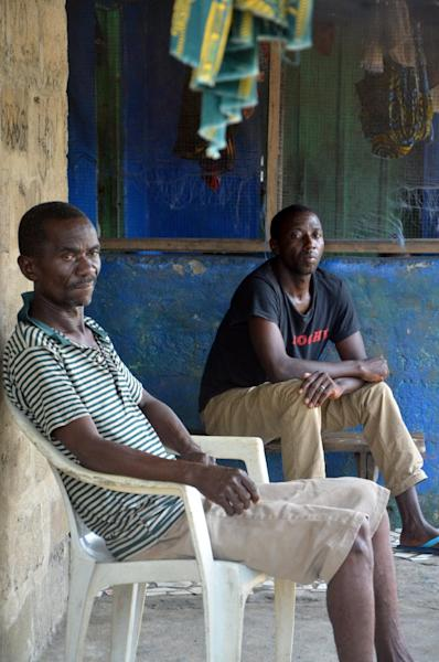 Two men infected with the Ebola virus wait for nurses to escort them to a hospital in Monrovia, August 25, 2014 (AFP Photo/Zoom Dosso)