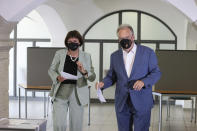 The governor of Saxony- Anhalt Reiner Haseloff, right, of Chancellor Angela Merkel's Christian Democratic Union party, CDU, and his wife Gabriele Haseloff, cast their vote for the state election of Saxony- Anhalt at a polling station in Wittenberg, Germany, Sunday, June 6, 2021. The election for the new state parliament in Saxony-Anhalt is the last state election before the national election in September 2021. (Robert Michael/dpa via AP)