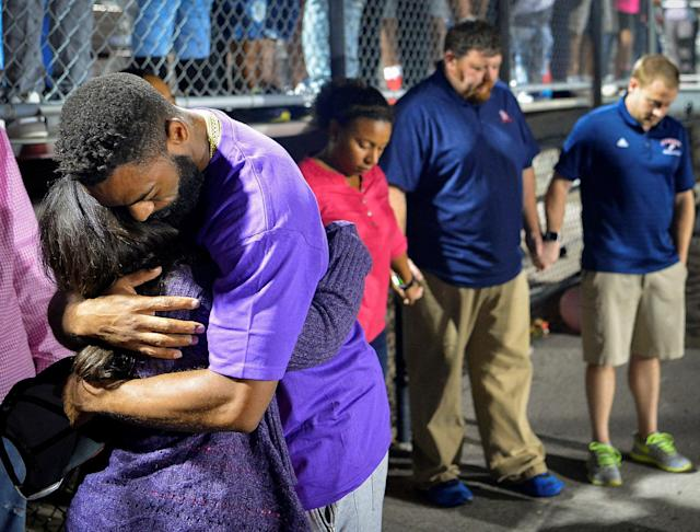 Shoshana Boyd (L) and Olympic sprinter Tyson Gay embrace during a candlelight vigil at Lafayette High School for their daughter Trinity Gay, who died in an exchange of gunfire early Sunday morning, in Lexington, Kentucky October 17, 2016. REUTERS/Bryan Woolston