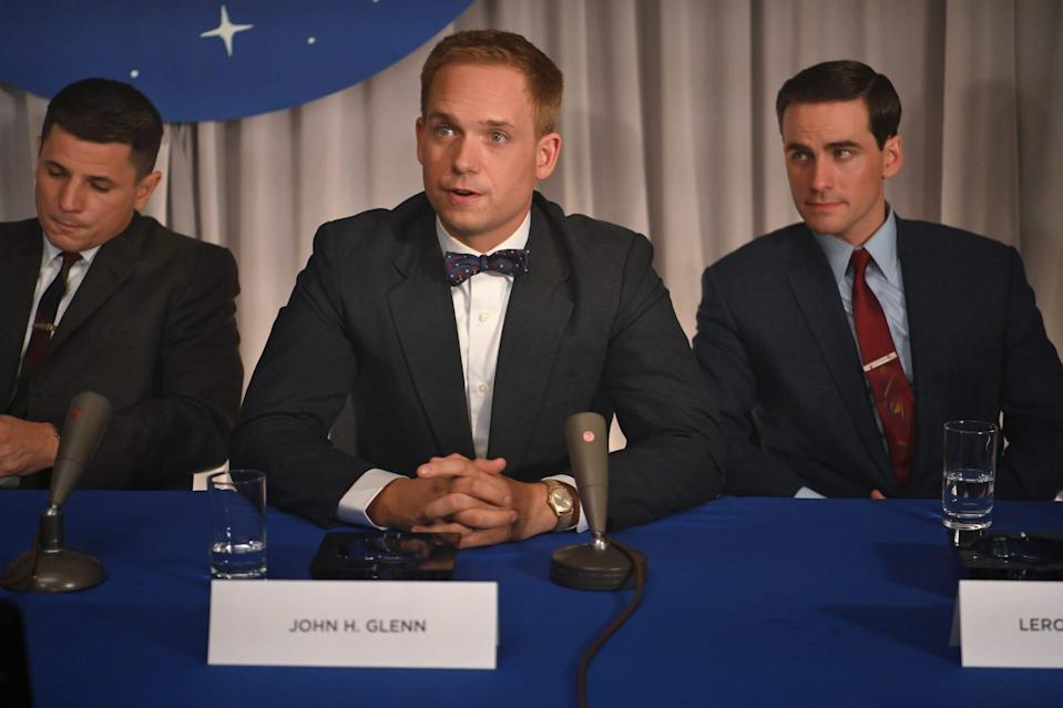 """John Glenn (Patrick J. Adams), seated between Virgil """"Gus"""" Grissom (Michael Trotter) and Leroy Gordon """"Gordo"""" Cooper (Colin O'Donoghue), speaks at a NASA press conference in Disney+'s 'The Right Stuff.'"""