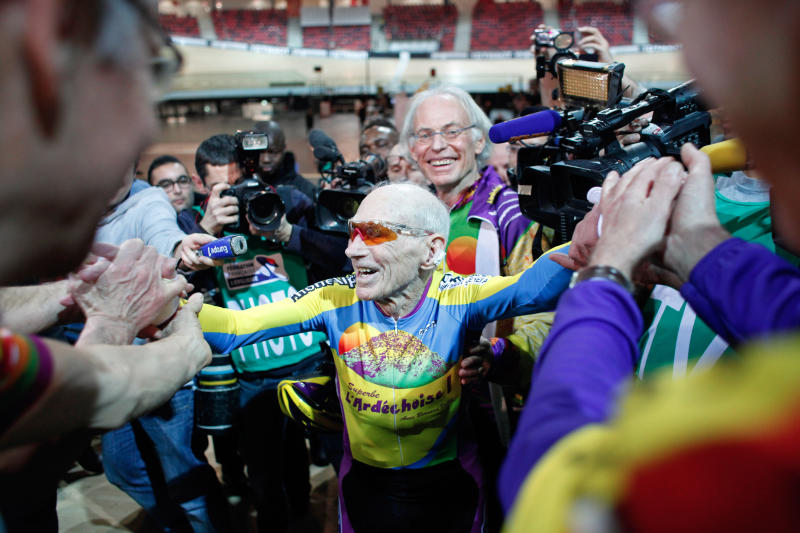 French cyclist Robert Marchand, aged 102, celebrates with fans after beating his record for distance cycled in one hour, at the velodrome of Saint-Quentin en Yvelines, outside Paris, Friday, Jan. 31, 2014. The 102-year-old broke his own world record in the over-100s category Friday, riding 26.927 kilometers (16.7 miles) in one hour, more than 2.5 kilometers better than his previous best time in the race against the clock two years ago. (AP Photo/Thibault Camus)