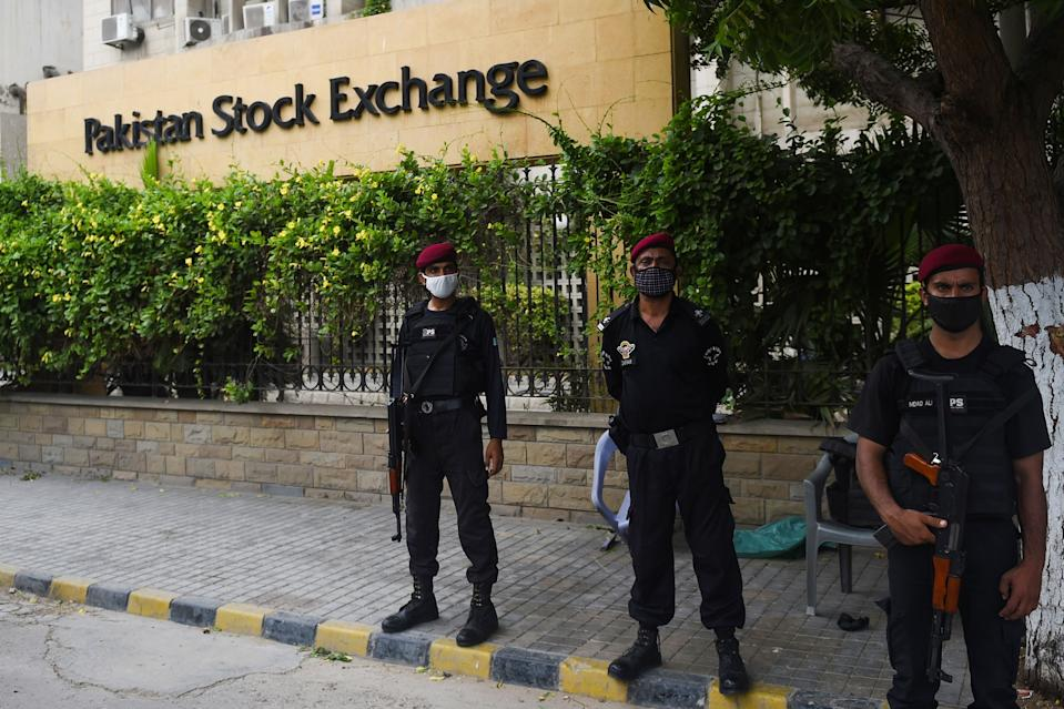 Policemen stand guard in front of the Pakistan Stock Exchange building following an attack by gunmen in Karachi on June 29, 2020. - At least six people were killed when gunmen attacked the Pakistan Stock Exchange in Karachi on June 29, with a policeman among the dead after the assailants opened fire and hurled a grenade at the trading floor, police said. (Photo by Rizwan TABASSUM / AFP) (Photo by RIZWAN TABASSUM/AFP via Getty Images)