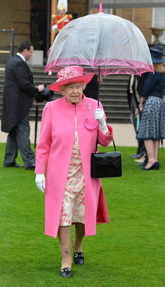 <p>The Queen sheltered from the rain in the garden of Buckingham Palace using a chic, pink-rimmed dome umbrella which matched the hue of her coat and hat perfectly. [Photo: PA] </p>