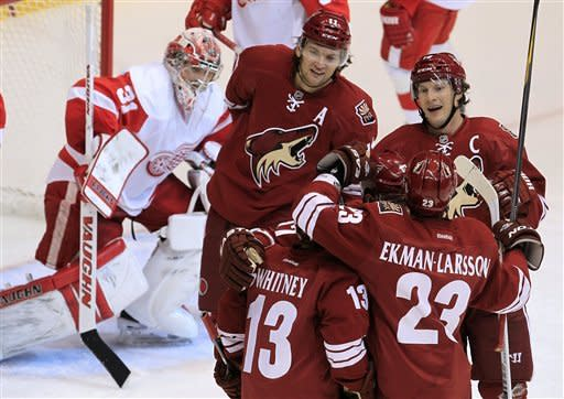 Phoenix Coyotes' Ray Whitney (13), Oliver Ekman-Larsson (23), of Sweden, and Shane Doan, top right, celebrate a goal by teammate Phoenix Coyotes' Martin Hanzal (11), of the Czech Republic, against Detroit Red Wings' Joey MacDonald (31) during the second period in an NHL hockey game Monday, Feb. 6, 2012, in Glendale, Ariz.(AP Photo/Ross D. Franklin)