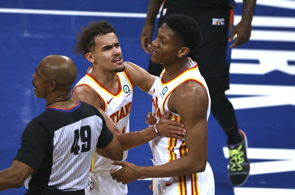 Atlanta Hawks' Trae Young (11) holds back De'Andre Hunter (12) after a foul was called against the New York Knicks during the third quarter of Game 2 in an NBA basketball first-round playoff series Wednesday, May 26, 2021, in New York. (Elsa/Pool Photo via AP)