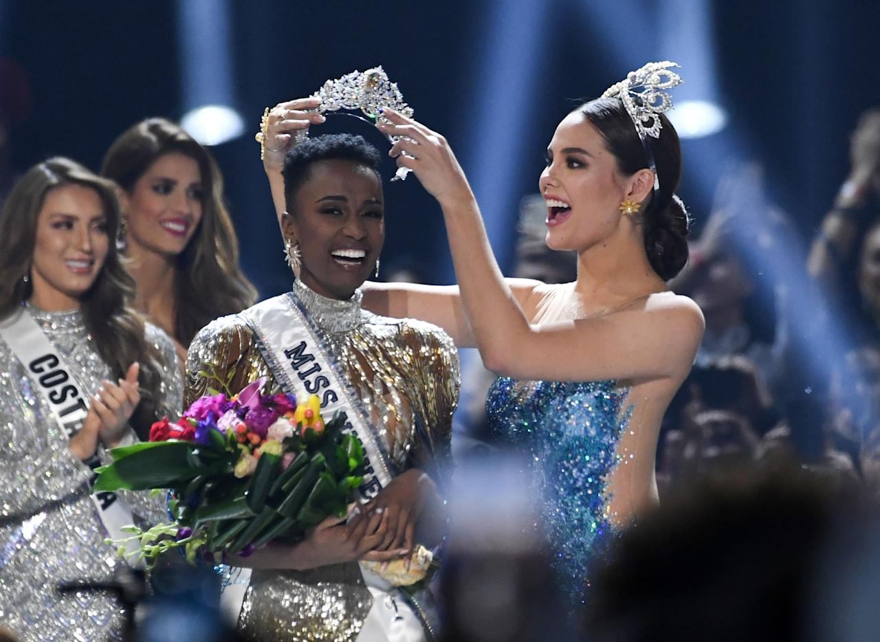 Miss Universe 2018 Philippines' Catriona Gray puts the crowns on the head of the new Miss Universe 2019 South Africa's Zozibini Tunzi on stage during the 2019 Miss Universe pageant at the Tyler Perry Studios in Atlanta, Georgia on December 8, 2019. (Photo by VALERIE MACON / AFP) (Photo by VALERIE MACON/AFP via Getty Images)