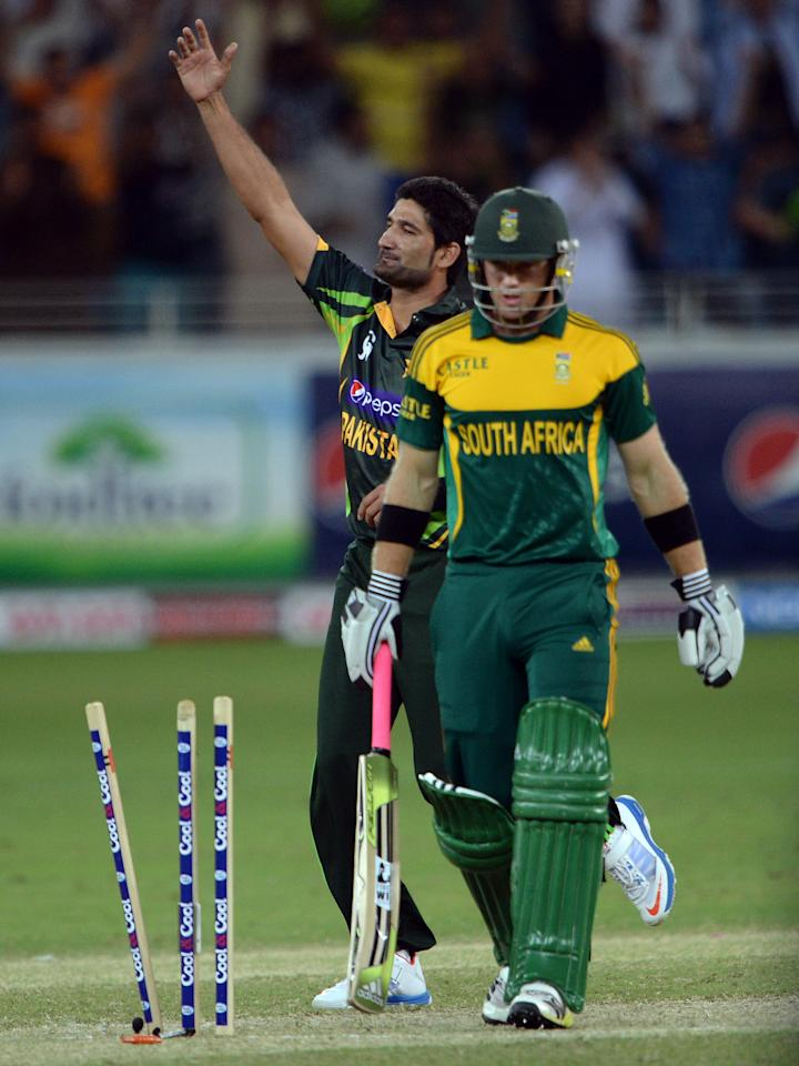 Pakistani bowler Sohail Tanvir (L) celebrates the clean bowl of South African opener Colin Ingram (R) during the second day-night international against South Africa in Dubai Cricket Stadium in Dubai on November 1, 2013. Pakistan captain Misbah-ul Haq won the toss and decided to bat. AFP PHOTO/ Asif HASSAN        (Photo credit should read ASIF HASSAN/AFP/Getty Images)