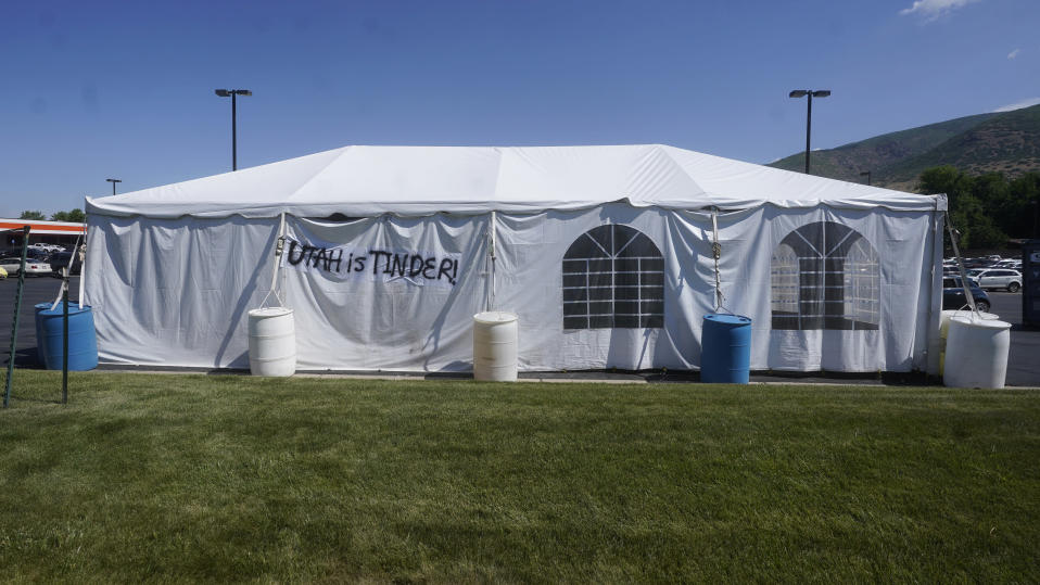"""A """"UTAH is TINDER"""" sign is placed on the side of a fireworks vendor tent Friday, June 25, 2021, in Centerville, Utah. Many Americans aching for normalcy as pandemic restrictions end are looking forward to traditional Fourth of July fireworks. But with a historic drought in the U.S. West and fears of another devastating wildfire season, officials are canceling displays, passing bans or begging for caution. (AP Photo/Rick Bowmer)"""