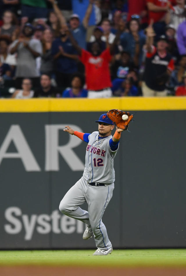 New York Mets center fielder Juan Lagares catches a ball hit by Atlanta Braves' Ender Inciarte after it bounced off the field, as fans cheer during the seventh inning of the team's baseball game against the Atlanta Braves, Wednesday, Aug.14, 2019, in Atlanta. Josh Donaldson scored from third on the play. (AP Photo/John Amis)