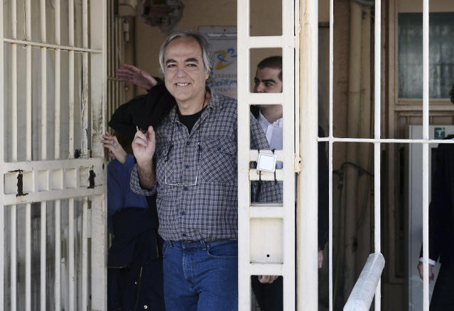 """FILE - In this Thursday, Nov. 9, 2017 file photo, Dimitris Koufodinas smiles as he leaves Korydallos prison in western Athens. A Greek far-left extremist serving 11 life terms for a string of murders is vowing to continue """"until the end"""" with a hunger strike after judges rejected his bid for new leave from prison. A lawyer representing Koufodinas, chief hit man for the November 17 group that killed 23 people from 1975-2000, says her client will also refuse medical assistance. (Yannis Kotsiaris/InTime News via AP, file)"""