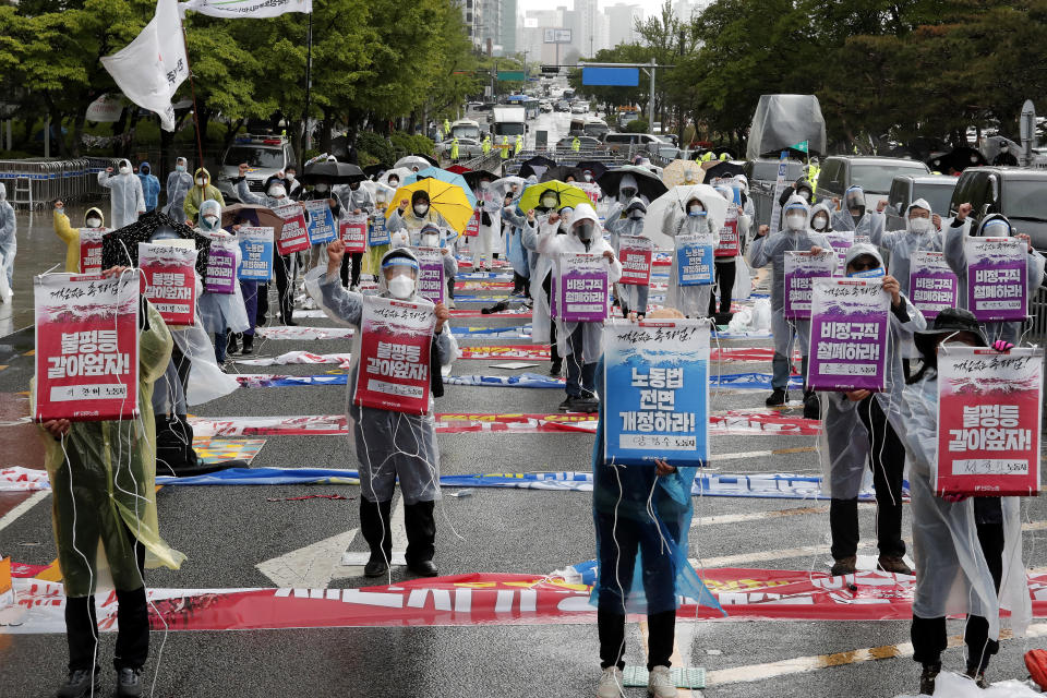 "Members of the Korean Confederation of Trade Unions stage a May Day rally demanding better working conditions and expanding labor rights in Seoul, South Korea, Saturday, May 1, 2021. The signs read: ""Let's solve inequality."" (AP Photo/Ahn Young-joon)"