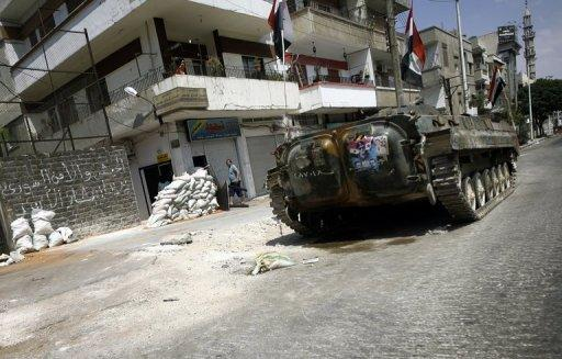 A Syrian military tank patrols the restive city of Homs