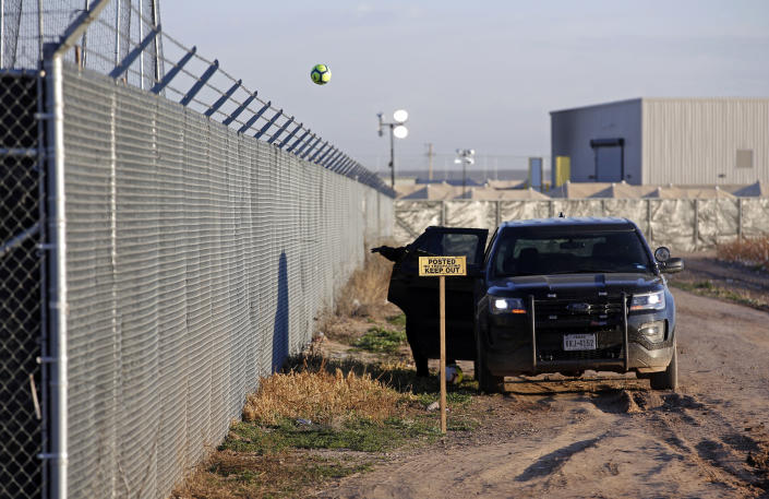 File- This Dec. 13, 2018, file photo shows a private security guard throwing a soccer ball back inside the Tornillo detention camp for migrant teens in Tornillo, Texas, The nonprofit group running what was once the nation's largest detention camp for migrant children confirmed it is closing down the facility and the last kids left on Friday, Jan. 11, 2019. (AP Photo/Andres Leighton, File)