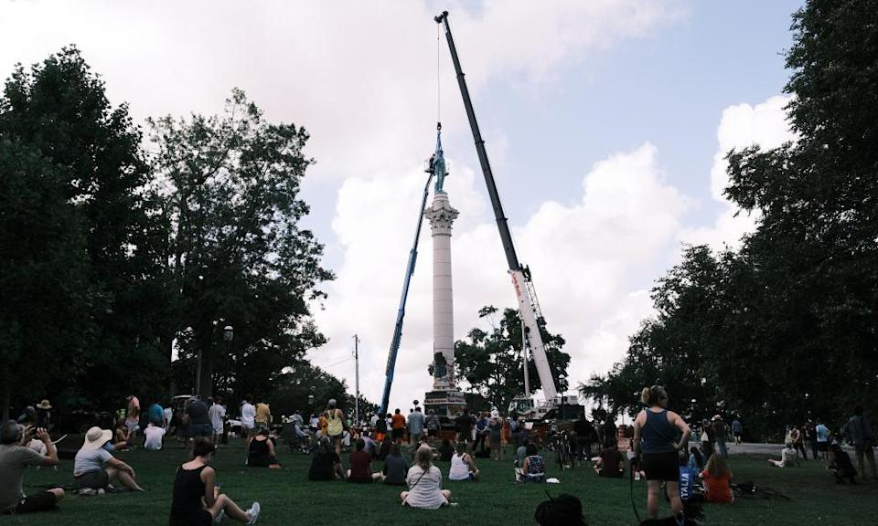 People watch as the Confederate soldiers and sailors statue is removed on 8 July 2020 in Richmond, Virginia, on the order of Mayor Levar Stoney.