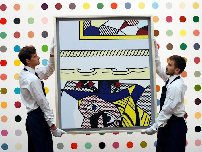 "Sotheby's employees carry a painting by Roy Lichtenstein called 'Two Paintings with Dado, 1983' during a press view at the auction rooms in London. <p class=""copyright"">Kirsty Wigglesworth/AP</p>"
