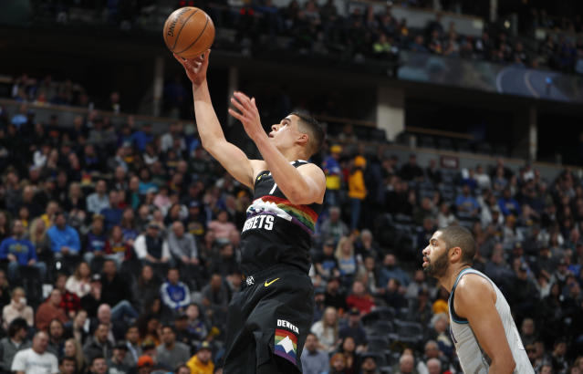 Denver Nuggets forward Michael Porter Jr., left, goes up for a basket past Charlotte Hornets guard Nicolas Batum during the first half of an NBA basketball game Wednesday, Jan. 15, 2020, in Denver. (AP Photo/David Zalubowski)