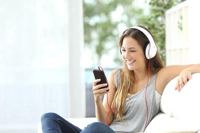 A woman wears headphones that are plugged into her smartphone.