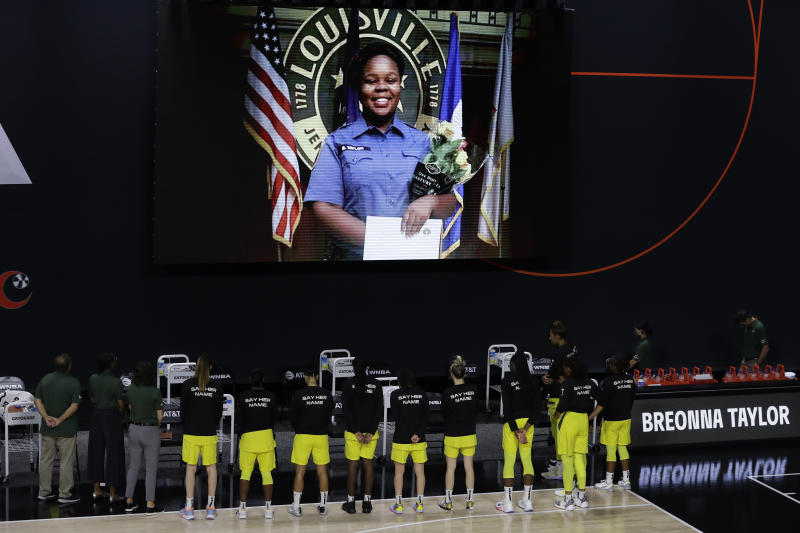 Seattle Storm players stand on the court sideline looking up at a photo of Breonna Taylor as an EMT.