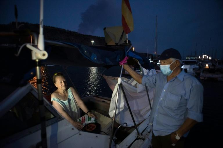 Pensioners Margaretha and Luis wait on their boat in the La Palma port of Tazacorte, where they fled following the eruption (AFP/JORGE GUERRERO)