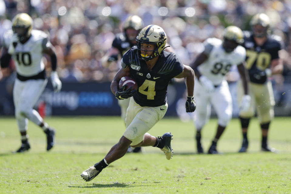 In this photo taken on Saturday, Sept. 7, 2019, Purdue wide receiver Rondale Moore (4) runs after a catch against Vanderbilt during the second half of an NCAA college football game in West Lafayette, Ind. First, Rondale Moore couldn't wait to get back on the field with Purdue. Then, after the COVID-19 pandemic hit and Big Ten leaders postponed the season, Purdue's speedy receiver couldn't wait to get to the NFL. Now, after announcing he would would skip this season to prepare for the draft, Moore is back on the practice field and the Boilermakers couldn't be happier.(AP Photo/Michael Conroy)
