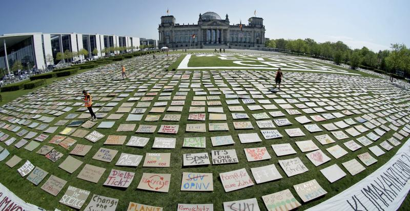 Placards cover a grassy field in front of government buildings in Berlin.