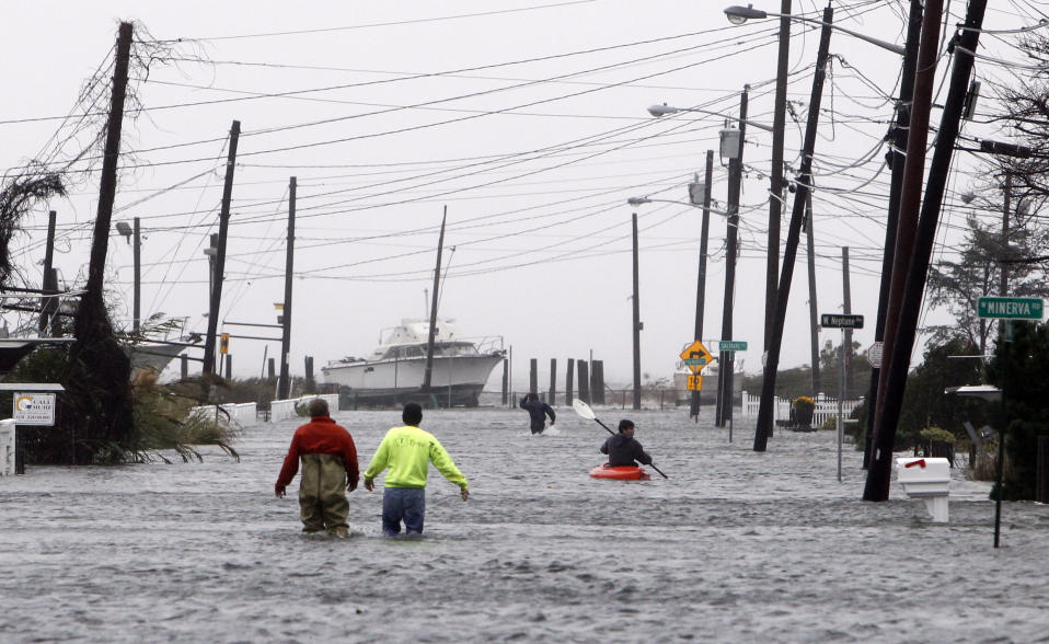 People wade and paddle down a flooded street as Hurricane Sandy approaches, Monday, Oct. 29, 2012, in Lindenhurst, N.Y. Gaining speed and power through the day, the storm knocked out electricity to more than 1 million people and figured to upend life for tens of millions more. (AP Photo/Jason DeCrow)