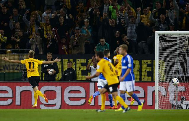 Dynamo Dresden's Justin Eilers (L) celebrates after he scored against Schalke 04 during their German soccer cup (DFB Pokal) match in Dresden August 18, 2014. REUTERS/Thomas Peter (GERMANY - Tags: SPORT SOCCER) DFB RULES PROHIBIT USE IN MMS SERVICES VIA HANDHELD DEVICES UNTIL TWO HOURS AFTER A MATCH AND ANY USAGE ON INTERNET OR ONLINE MEDIA SIMULATING VIDEO FOOTAGE DURING THE MATCH