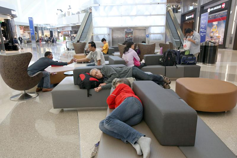 In this Monday, May 5, 2014 photo, passengers sleep on new couches in the Tom Bradley International Terminal at Los Angeles International Airport (LAX). TBIT is a completed part of improvements at the aging airport, which is scheduled to get newly surfaced roads, upgraded restaurants with Los Angeles themes, and some terminal makeovers that will infuse more sunlight into otherwise cave-like interiors. Also in the plans are new bathrooms and, that essential for travelers, more outlets and USB ports for charging electronic devices. (AP Photo/Nick Ut )