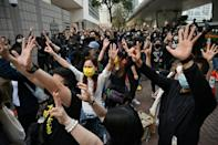 Pro-democracy activists in Hong Kong raise their hands to defy authorities and show support for dissidents facing suversion charges outside the West Kowloon court in Hong Kong